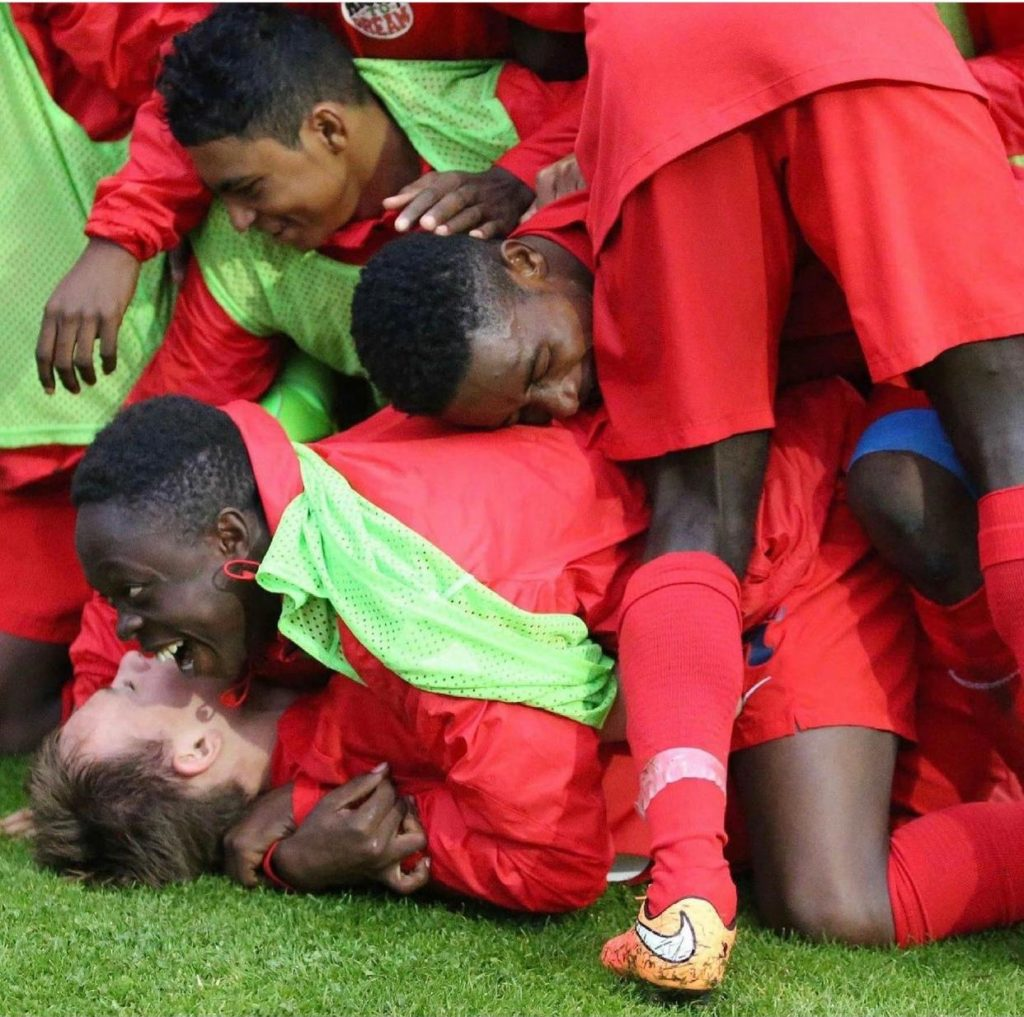 Right to Dream academy players mob Damsgaard after scoring for the Ghanaian academy in an international tournament